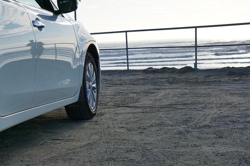Carro estacionado na beira da praia